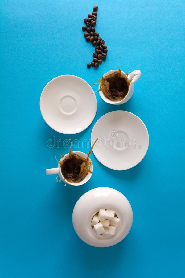 Cups with espresso splash, saucers, teaspoon and coffee beans on blue paper background. Good morning concept stock photos