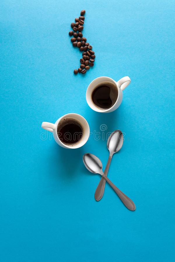 Cups with espresso splash, saucers, teaspoon and coffee beans on blue paper background. Good morning concept. Art food style.  stock photography