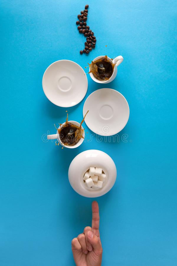 Cups with espresso splash, saucers, teaspoon and coffee beans on blue paper background. Good morning concept. Art food style stock photo