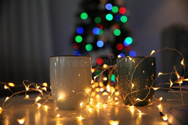 Cups, fairy lights and blurred Christmas tree in room. Cups, fairy lights and blurred Christmas tree on background royalty free stock images