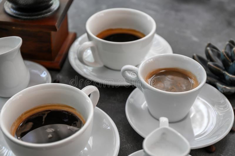 Cups of fresh aromatic coffee on grey background royalty free stock images