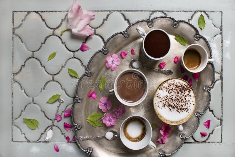 Cups of hot aromatic coffee and chocolate. Espresso, espresso macchiato and latte. On the background of the old table, antique tea royalty free stock photos