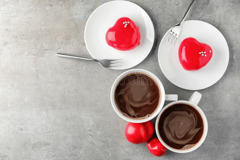 Cups of hot chocolate with heart shaped desserts on grey table stock photos