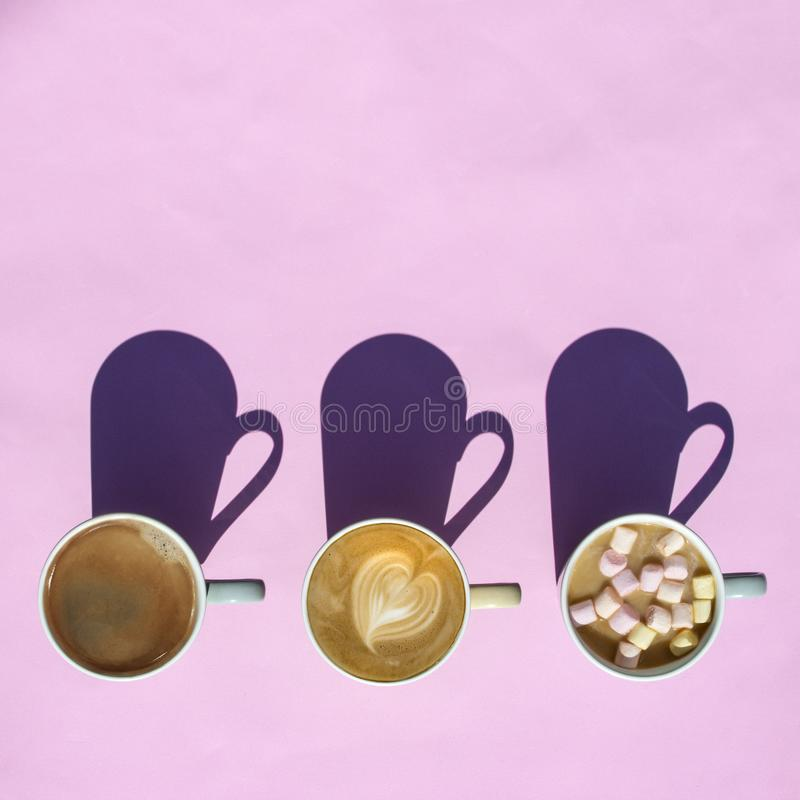 Cups of hot coffee with marshmallows, heart with shadow on pink background. Top view, flat lay. Minimal style. Art design royalty free stock images