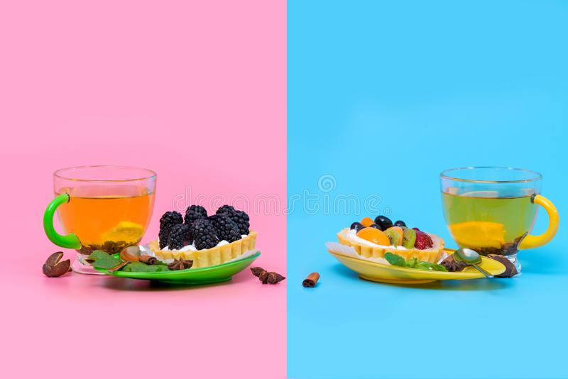 Cups of hot spicy lemon tea with fruit pastries royalty free stock photos