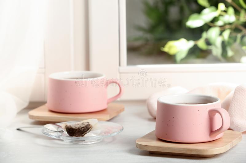 Cups of hot tea with wooden coasters on window. Sill stock images