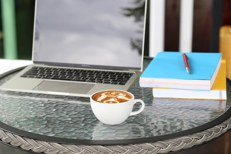 Cups of latte coffee with laptop working in coffee shop royalty free stock photos