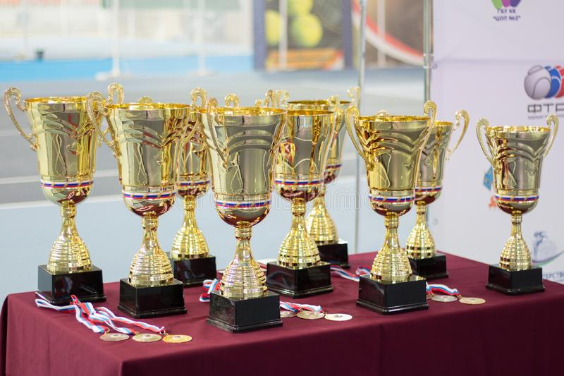 Cups and medals for the winners of the tennis tournament. Cups and medals for the winners of the children`s tennis tournament royalty free stock photography