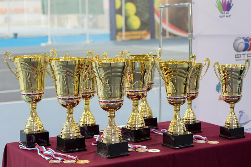 Cups and medals for the winners of the tennis tournament. Cups and medals for the winners of the children`s tennis tournament stock photography