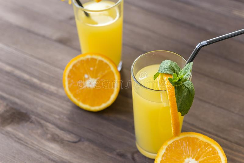 cups of orange juice with a straw, sprig of mint, half a fresh orange on a brown wooden background stock images