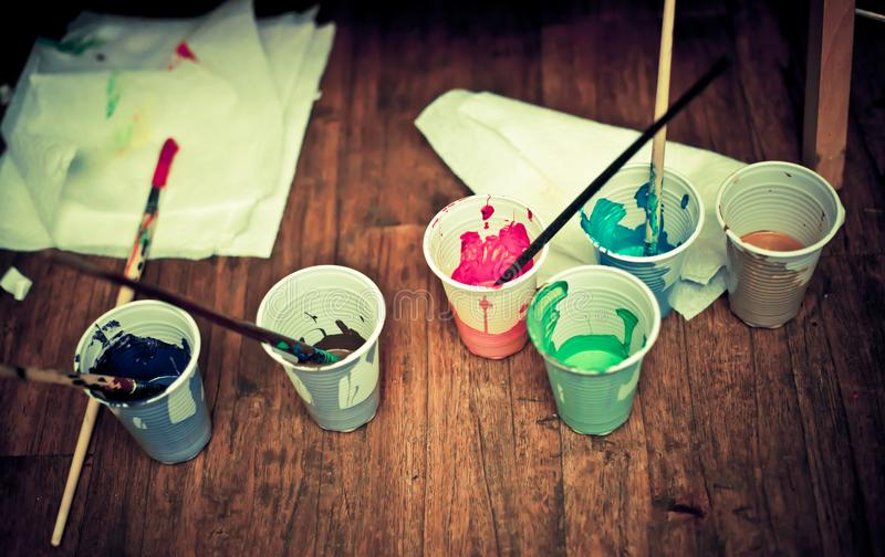 Cups with paint and brushes on the table royalty free stock photography