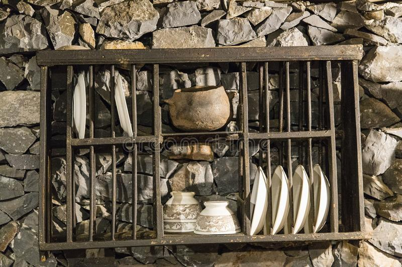 Cups and saucers in abandoned farmhouse La Gomera, Spain. Farmers wall rack with cup and saucers in empty farmers house La Gomera, Spain stock photography