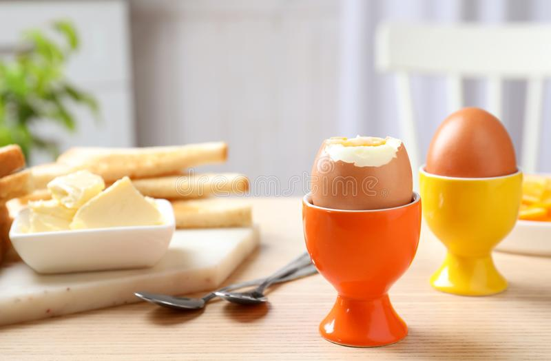 Cups with soft boiled eggs on wooden table. Healthy breakfast stock images