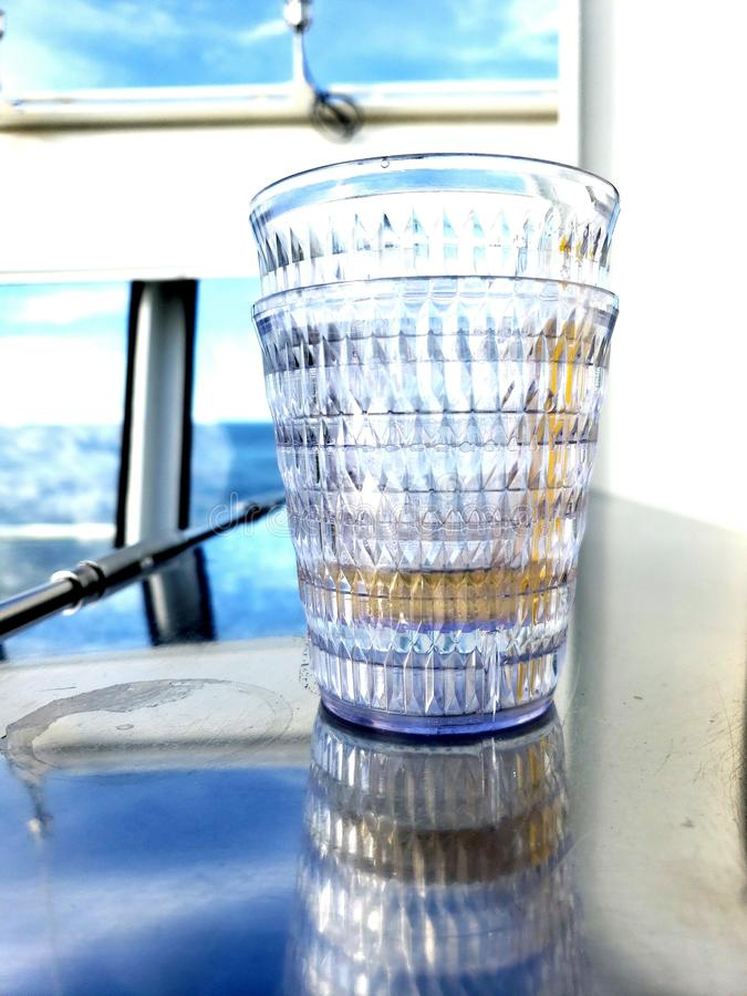 Cups stacked on a counter on a boat with liquid left in them royalty free stock photos