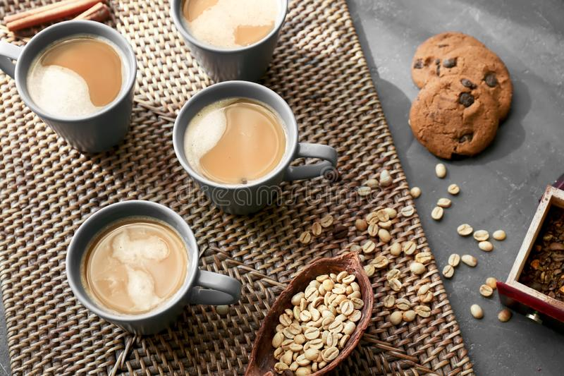 Cups with tasty aromatic coffee and cookies on table stock image