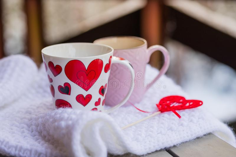 Cups of tea or coffee with steam,heart shape on blurred background. Valentine`s day celebration or love concept. Copy stock image