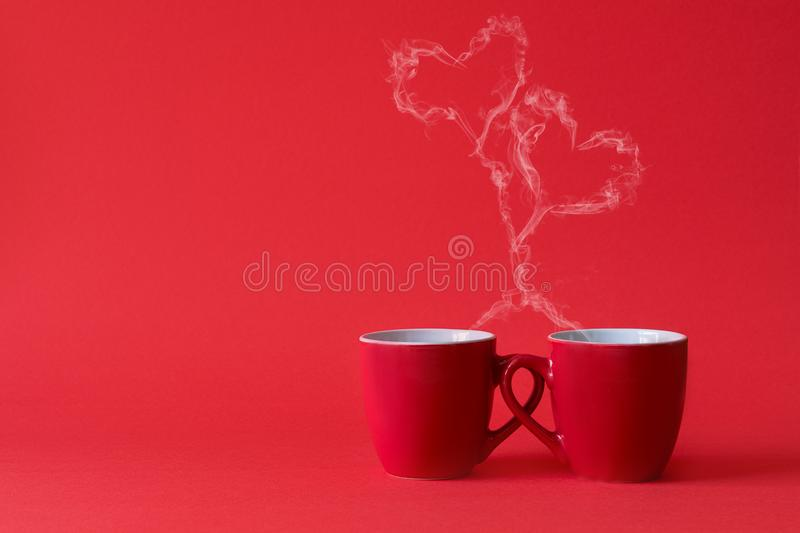 Cups of tea or coffee with steam in two heart shape on red background. Valentine`s day celebration or love concept. Copy space.  royalty free stock photography