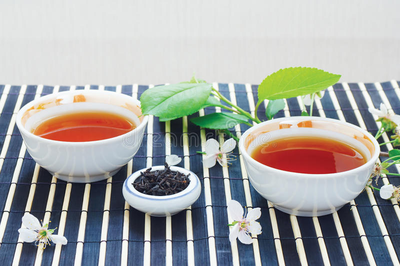 Cups of tea, jar of tea leaves and cherry blossoms royalty free stock photos