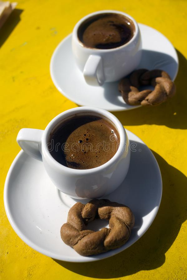 A cups of traditional greek coffee with cookie  served in all over the Greece stock images