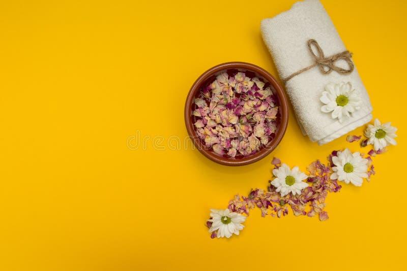 Cura del corpo, fiore, acqua e un asciugamano fotografia stock