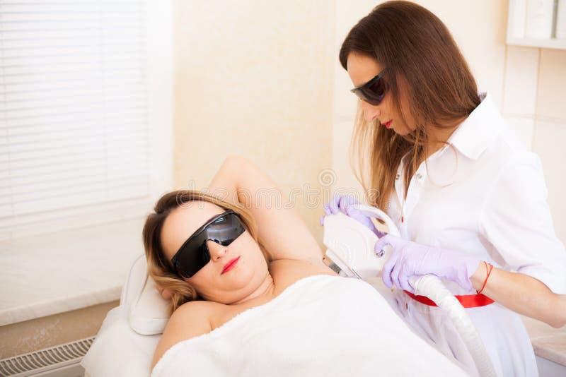 Cura del corpo La bella ragazza si trova nell'ufficio di un estetista negli occhiali di protezione da irradiamento del laser, le  fotografia stock