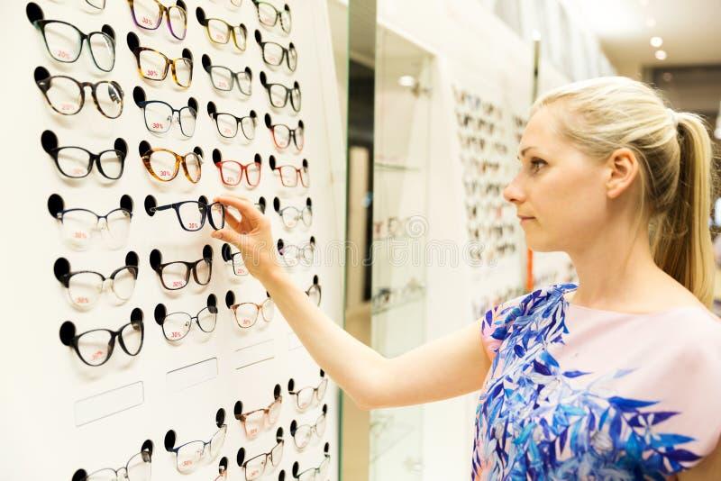Cura dell'occhio - giovane donna che sceglie i nuovi vetri nel deposito dell'ottico immagini stock