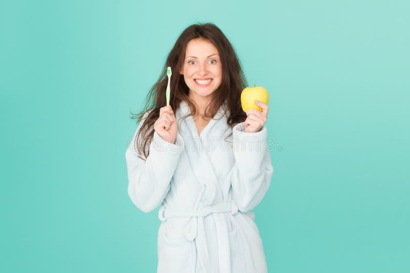 Cura dentale Igiene orale Spazzolino da denti e mela della tenuta dell'accappatoio della donna L'igiene personale Pulisca i denti fotografia stock