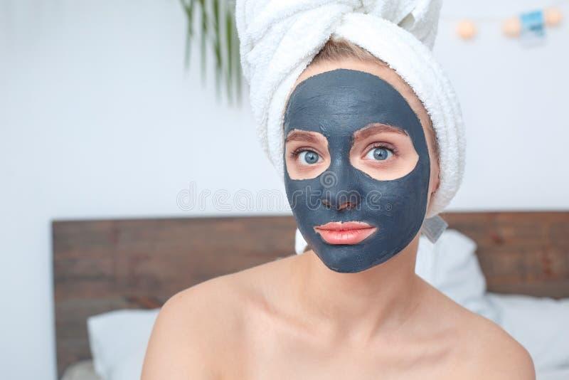 Cura di bellezza della giovane donna a casa che si siede con una maschera sul fronte che guarda il primo piano emozionante della  fotografia stock