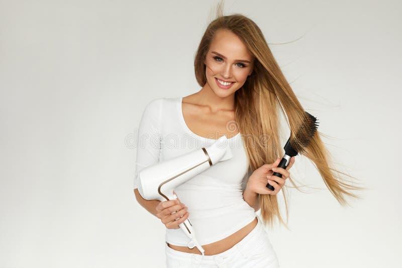 Cura di capelli Donna che asciuga bei capelli lunghi facendo uso dell'essiccatore immagini stock libere da diritti