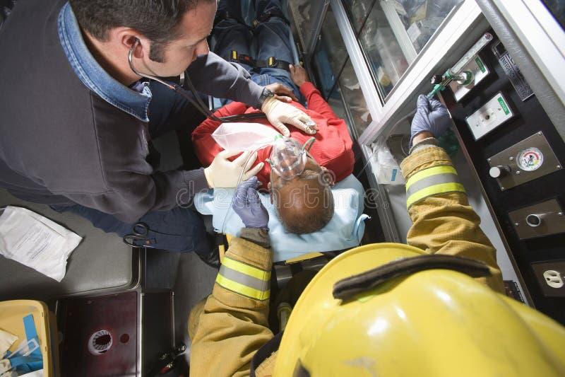 Cura di And Doctor Taking del pompiere dell'uomo senior fotografie stock