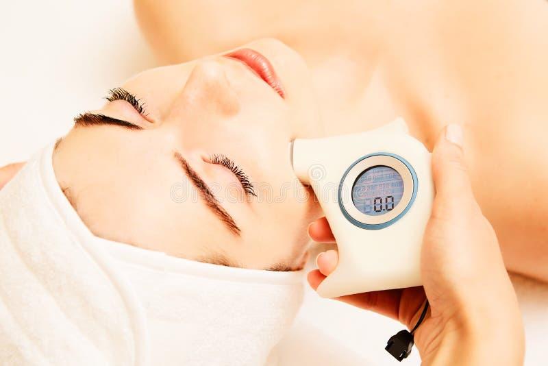 Cura di pelle Bella donna in buona salute che ottiene la sua pelle Analized dal cosmetologo, facendo uso dell'analizzatore della  fotografie stock