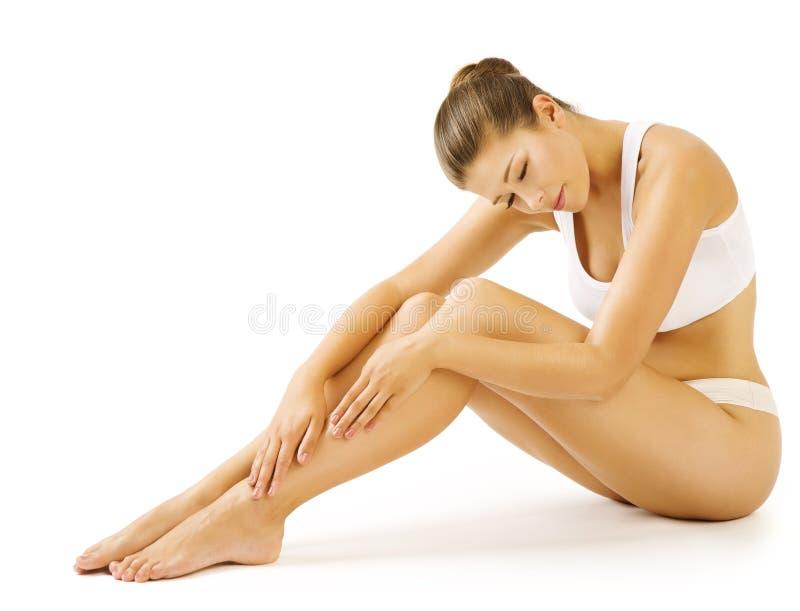 Cura di pelle di bellezza del corpo delle gambe della donna, biancheria intima bianca femminile immagini stock