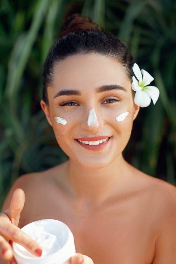 Cura di pelle Concetto di bellezza Giovane donna graziosa che tiene crema cosmetica Pelle molle e spalle nude fotografie stock