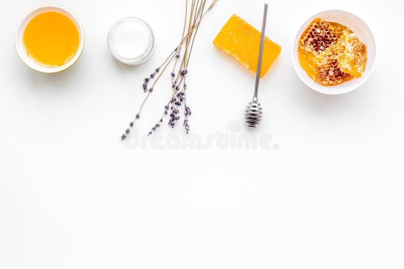 Cura di pelle delicata e di theraphy aromatico Insieme della stazione termale basato su miele sullo spazio bianco della copia di  immagine stock