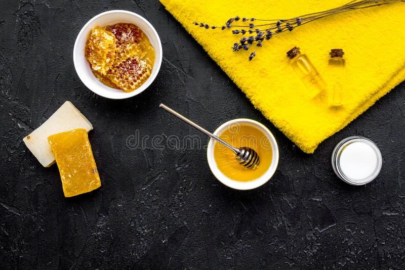 Cura di pelle delicata e di theraphy aromatico Insieme della stazione termale basato su miele sullo spazio nero di vista superior immagini stock