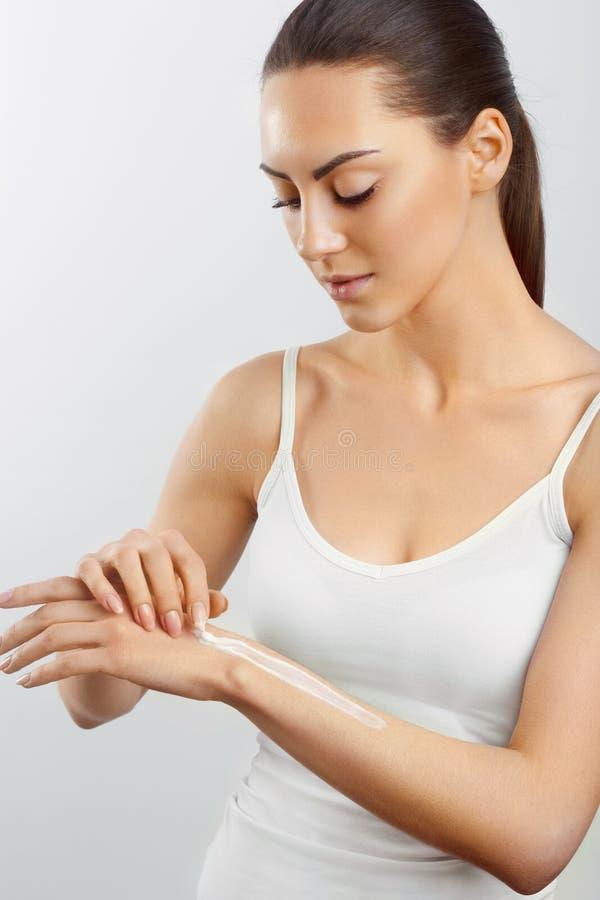Cura di pelle della mano Bella donna che applica crema d'idratazione sulla sua mano La lozione per le mani delle donne Concetto d immagine stock libera da diritti
