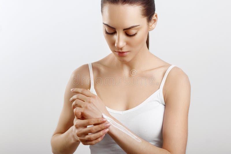 Cura di pelle della mano Chiuda su delle mani femminili che applicano la crema, lozione Belle mani della donna con il manicure ro fotografia stock libera da diritti