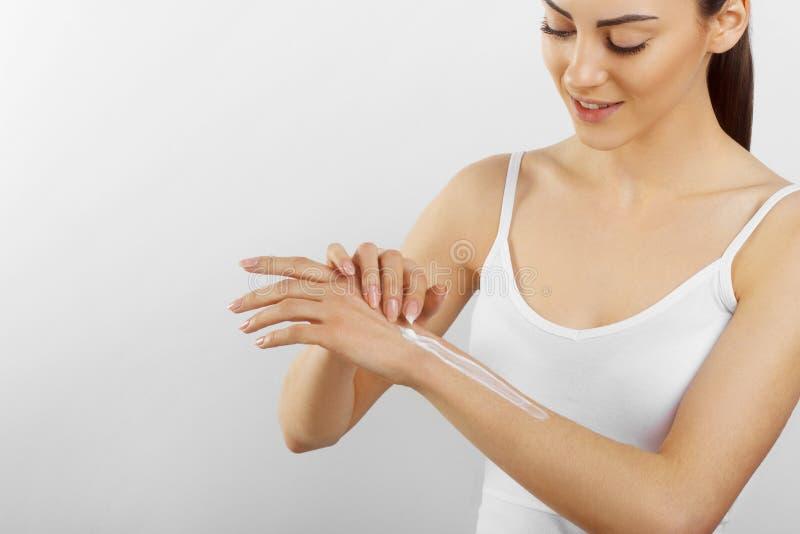 Cura di pelle della mano Chiuda su delle mani femminili che applicano la crema, lozione Belle mani della donna con il manicure ro fotografia stock