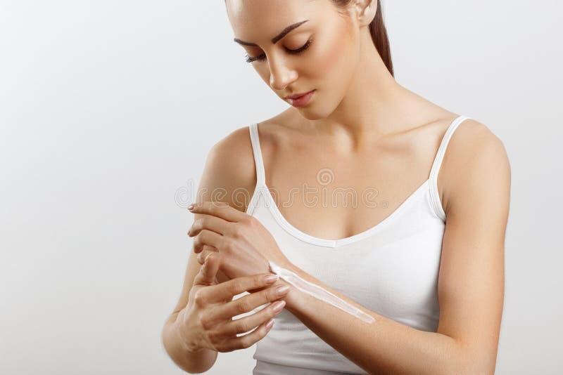 Cura di pelle della mano Chiuda su delle mani femminili che applicano la crema, lozione Belle mani della donna con il manicure ro fotografie stock