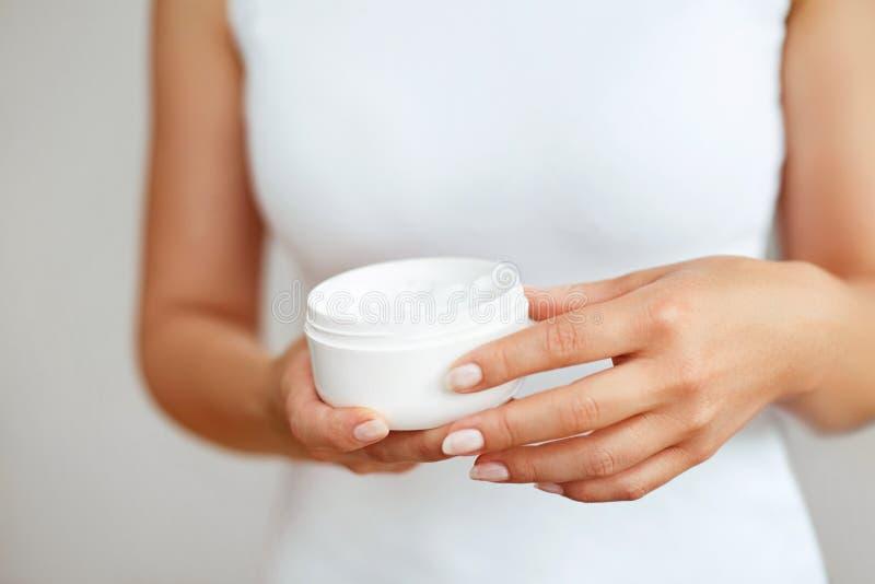 Cura di pelle della mano Chiuda su delle mani femminili che tengono la metropolitana crema, belle mani della donna con le unghie  fotografia stock libera da diritti