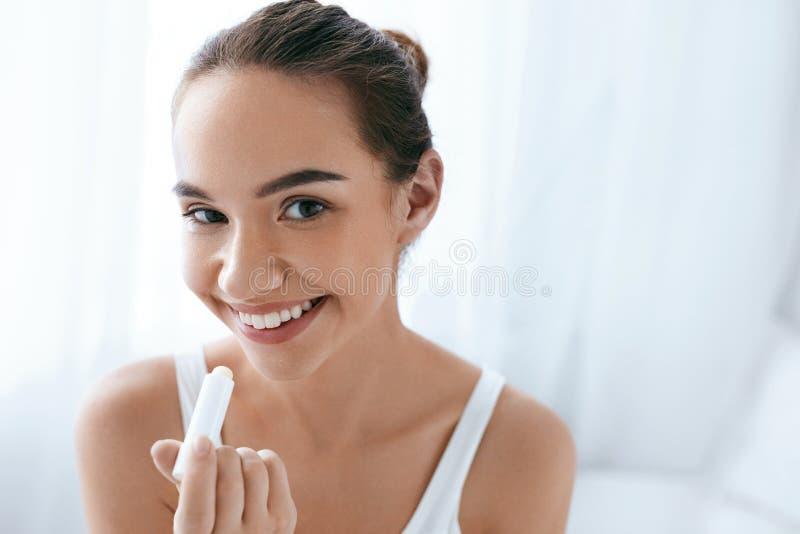 Cura di pelle delle labbra Bella donna che applica il balsamo di orlo bellezza fotografie stock