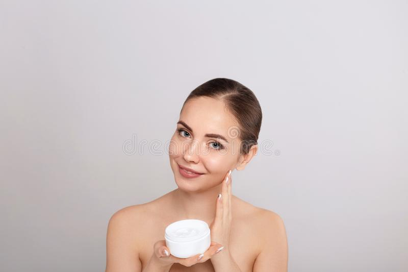 Cura di pelle Donna con bellezza naturale del fronte che tiene crema facciale immagini stock libere da diritti
