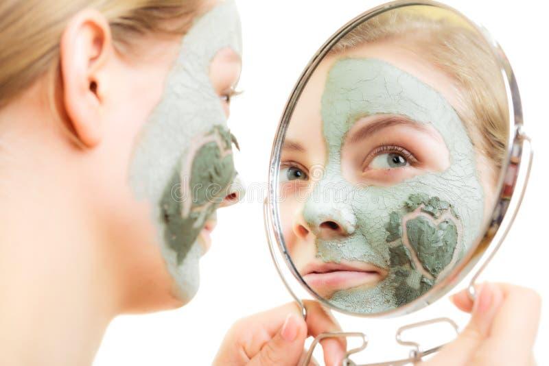 Cura di pelle. Donna nella maschera del fango dell'argilla sul fronte. Bellezza. immagine stock