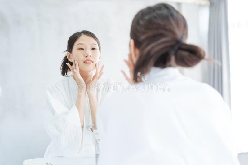 Cura di pelle femminile Giovane donna asiatica che tocca il suo fronte e che guarda per rispecchiarsi in bagno immagine stock