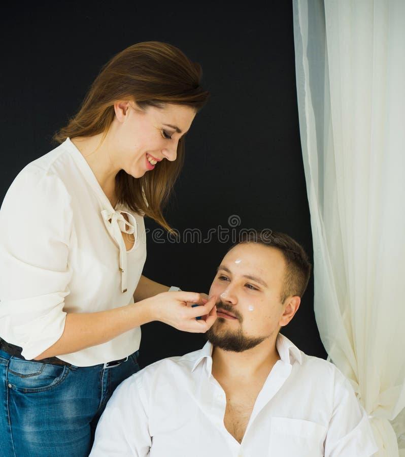 Cura di pelle La bella donna applica l'idratante sul fronte di un uomo sorridente Protezione e cura di pelle fotografie stock libere da diritti