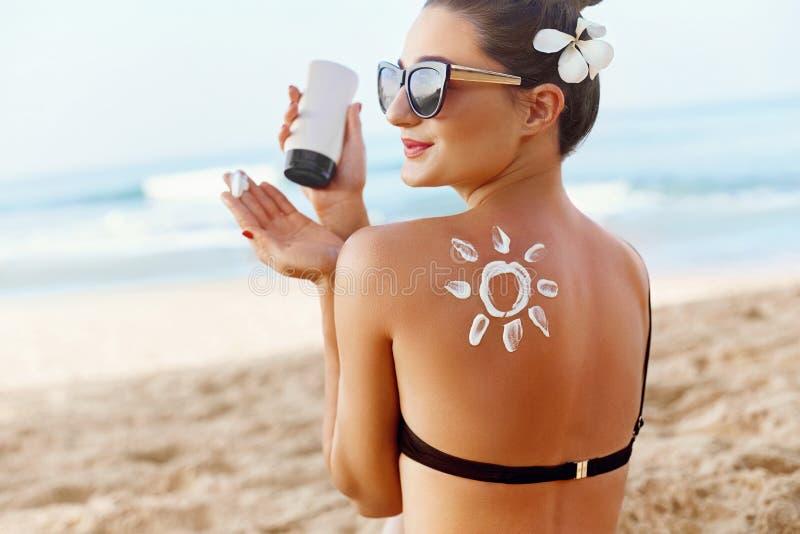 Cura di pelle Protezione di Sun La donna applica la crema del sole Ragazza che tiene Sunblock d'idratazione Donna con lozione sol immagini stock libere da diritti
