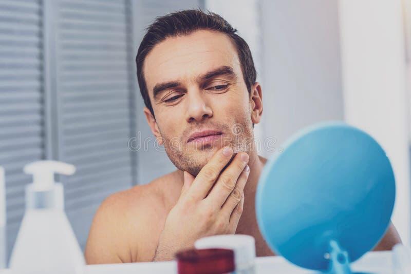 Cura di presa di modello maschio della sua pelle prima della sessione di foto immagini stock libere da diritti