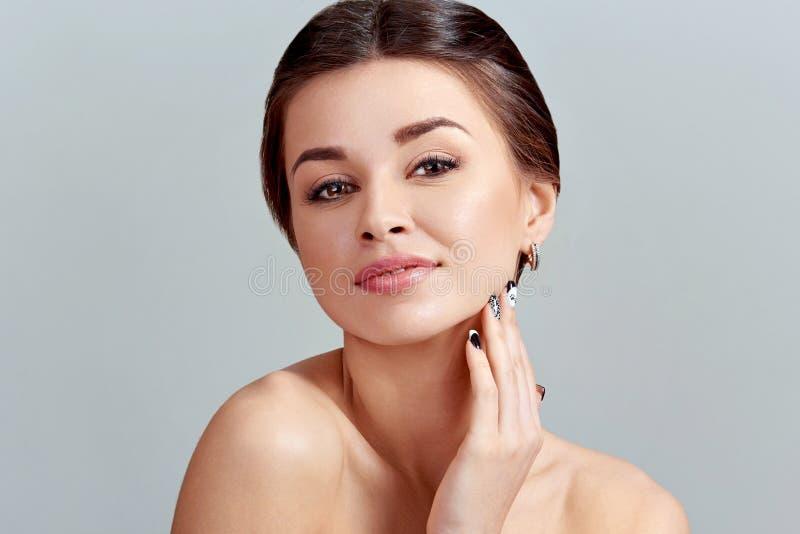 Cura facciale Crema d'applicazione femminile e sorridere Fronte di bellezza Ritratto della giovane donna immagini stock libere da diritti