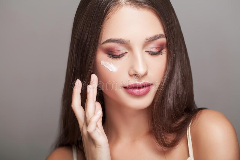 Cura facciale Ritratto della giovane donna sexy con le gocce del cosmetico immagine stock libera da diritti