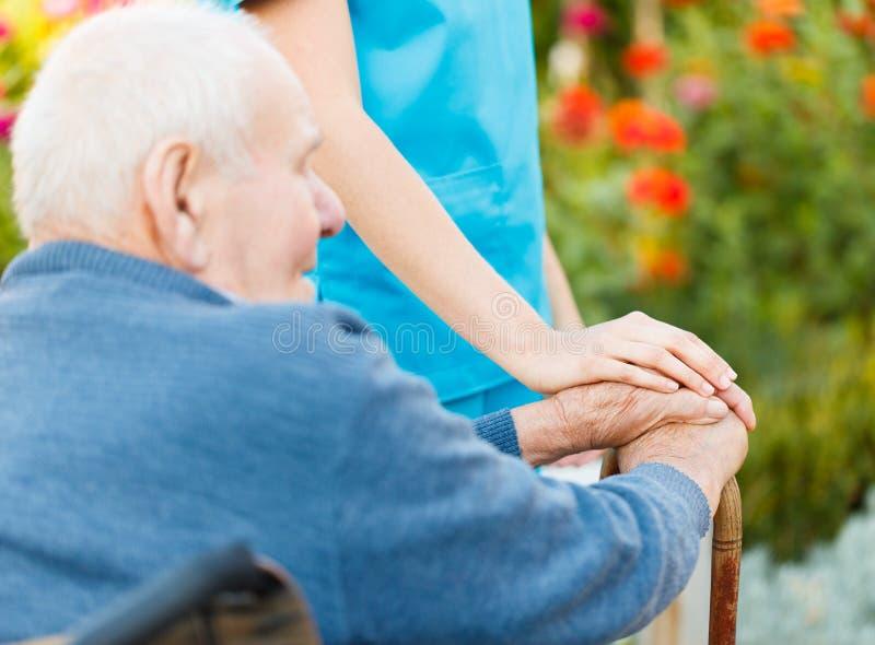 Cura per gli anziani in sedia a rotelle fotografia stock